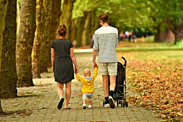A couple walking their toddler.