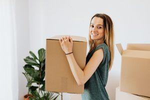 a woman carrying a box - cheap packing supplies