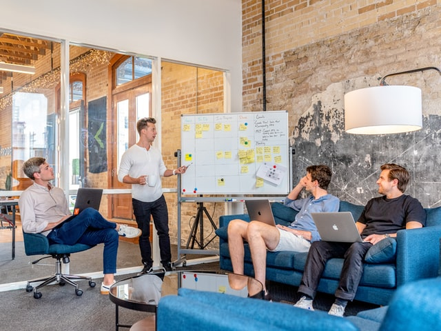 Four men in an office with a whiteboard planning an office space downsizing