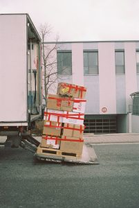 A pile of cardboard boxes being loaded onto a moving truck before moving from Denver to Seattle.