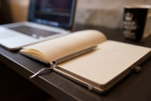 An open notebook and a pen to write down a strategy for your moving from Denver to Manhattan.